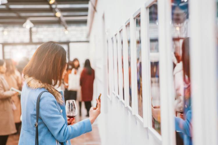A woman in an art gallery takes a picture of an art piece title card while holding a glass of red wine