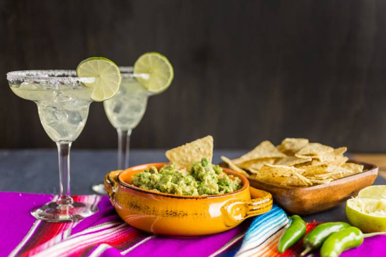 A display of margaritas and guacamole with chips on a sarape