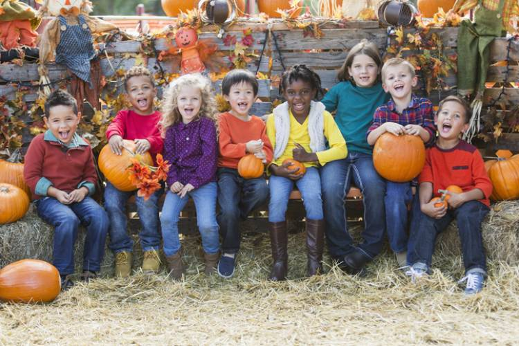 Eight kids smile and laugh on hay bales at a harvest festival